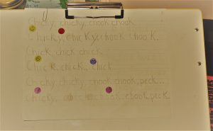 Difficult to see photo of a poem copied by a child on lined paper.