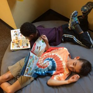 Two boys laying on a big bean bag chair reading.
