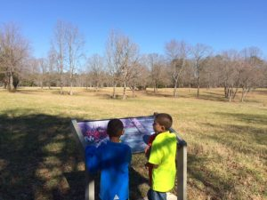 Two boys standing at interpretive sign and overlooking Cowpens Battlefield.