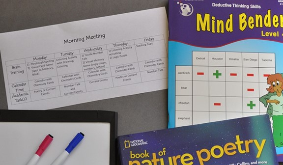 Morning meeting schedule, books, and whiteboard with markers