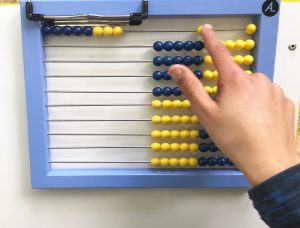 Hand moving the 9th bead over on the abacus.