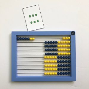 Abacus showing 7, which is one more than the dot pattern card showing 6.