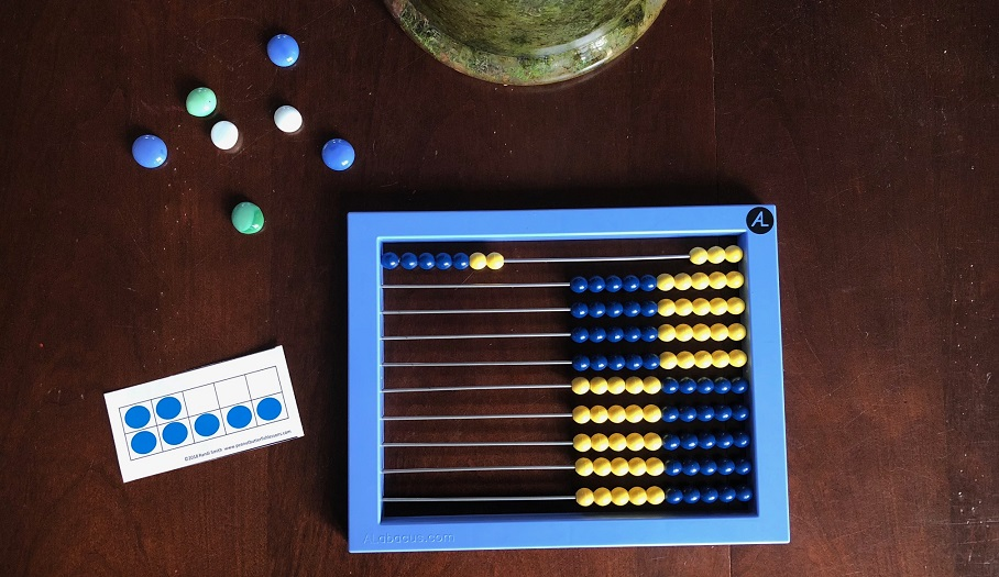 Abacus showing 7 with 10 frame card and 7 colored rocks