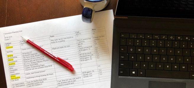 Homeschool Curriculum Plannin Guide next to a computer