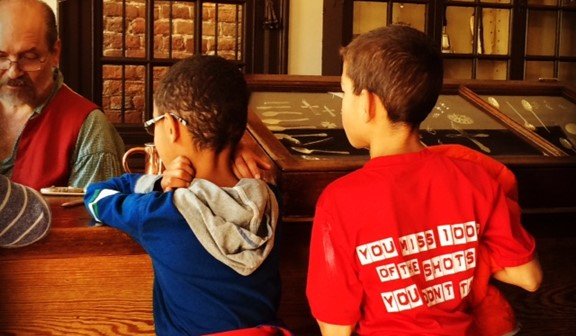 Two boys looking at a jeweler making jewelry at Colonial Williamsburg