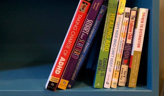 9 books about ADHD on a book shelf
