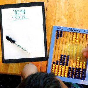 Abacus from the RightStart Math curriculum with a whiteboard to work out the problem.
