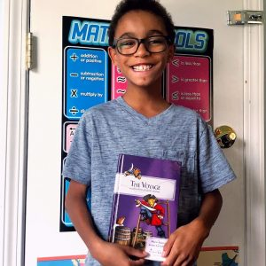 Smiling boy holding a read from the All About Reading program.
