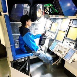 Boy inside a replica of the space shuttle cockpit.