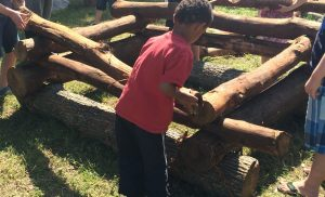 Children stacking logs to build a cabin at a living history museum.