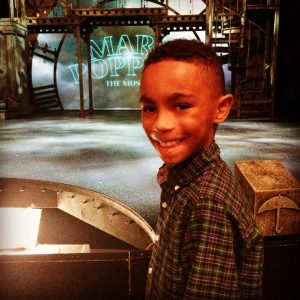 Boy standing in front of stage on family field trip to see Mary Poppins.