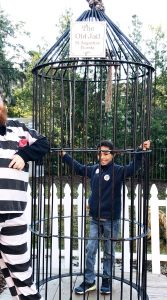 Boy standing in an old jail cell outside with a jailer in costume next to him.