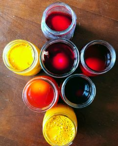 Seven mason jars with dyes and eggs in them.