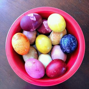 Eggs in a variety of colors grouped in a red bowl sitting on a table.