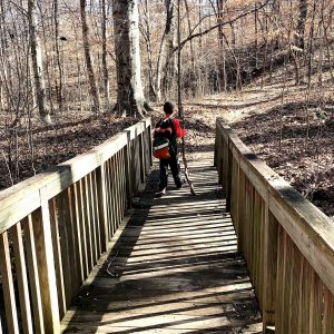 Boy crossing a wooden bridge while hiking