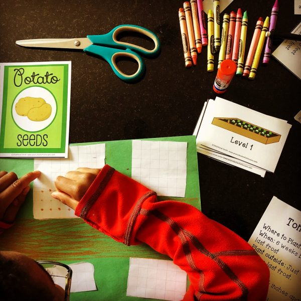 Child working on the project iwth scissors, crayons, printable cards, and paper
