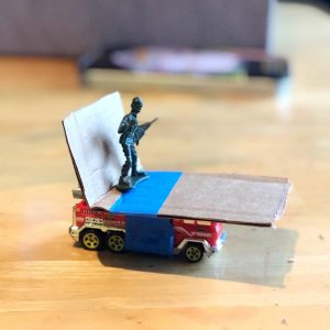 Matchbox car with cardboard seat taped on top and toy soldier standing on it.