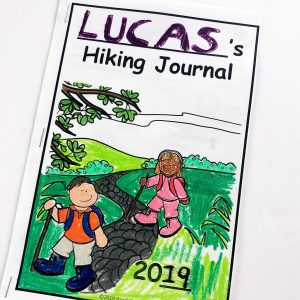 Hand colored cover of a hiking journal showing two children hiking on a trail.