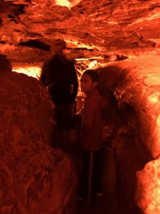 People walking through a narrow slot canyon with low ceilings lit in orange light.
