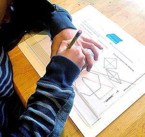 Boy using a T square and triangle to make geometric shapes on a paper.