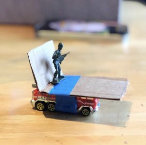 Toy soldier on a cardboard on a matchbox car as part of an experiment about force.