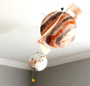 Painted styrofoam planets hanging from a ceiling.