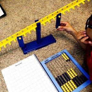 Boy working with math balance, abacus and worksheet.