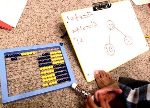 Boy working with abacus, part-part whole circles and equations on whiteboard.