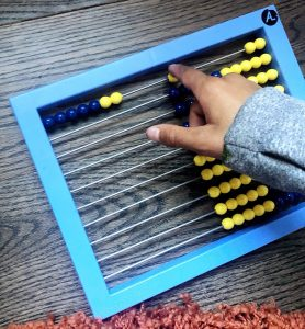 Hand moving beads on an abacus one at a time.