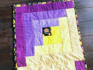 Purple and yellow log cabin quilt square.