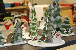 Scenes with Christmas trees and snowmen set out on a table.
