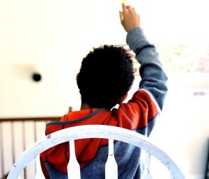Back view of child with hand up in air 'writing' a word.