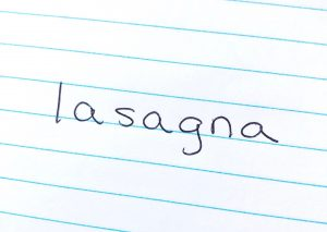 The word 'lasagna' written on a piece of notebook paper in black pen.