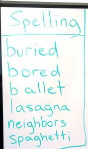 List of spelling words written on white board with green marker, including buried, bored, ballet, lasagna, neighbors, and spaghetti.
