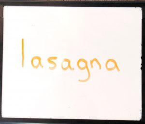 White board with the word 'lasagna' on written on it in orange marker.