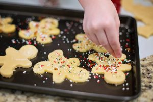 Baking sheet with gingerbread man cut-out cookies and a hand decorarting them.