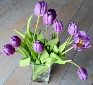 View from above of a vase with 10 purple tulips.