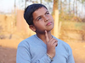 Boy with index finger to chin looking up with thoughtful expression.